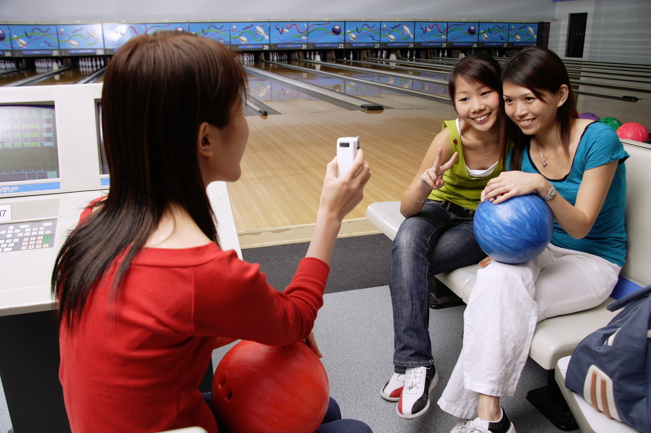 Women in bowling alley, posing for friends phone camera