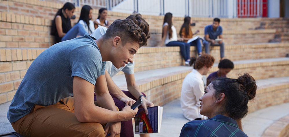 Students having conversation in auditorium outside