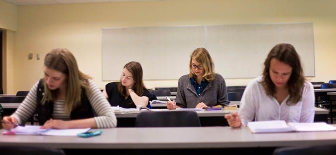 Female College Students at desks in a classroom