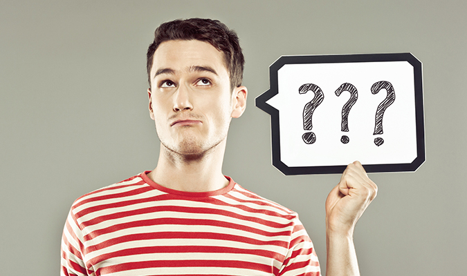 Young man holding speech bubble with question marks