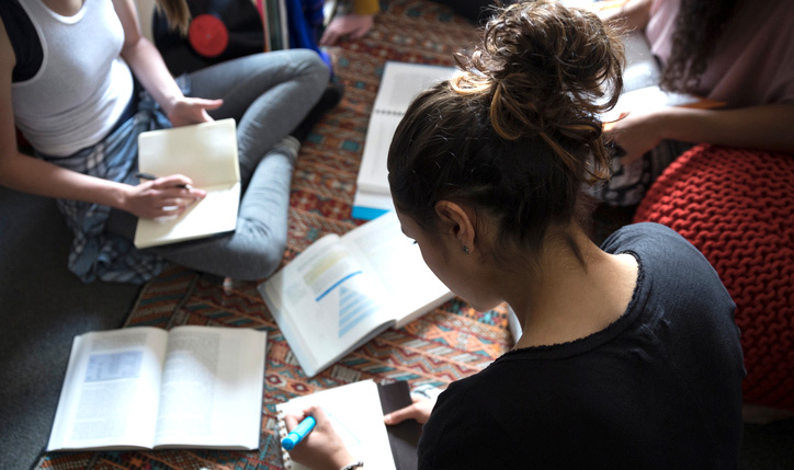 Female college students studying on floor in dorm room