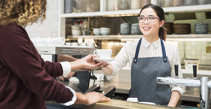 Woman handing coffee cup to customer in cafe. Coffee shop counter, service, coffee bar.
