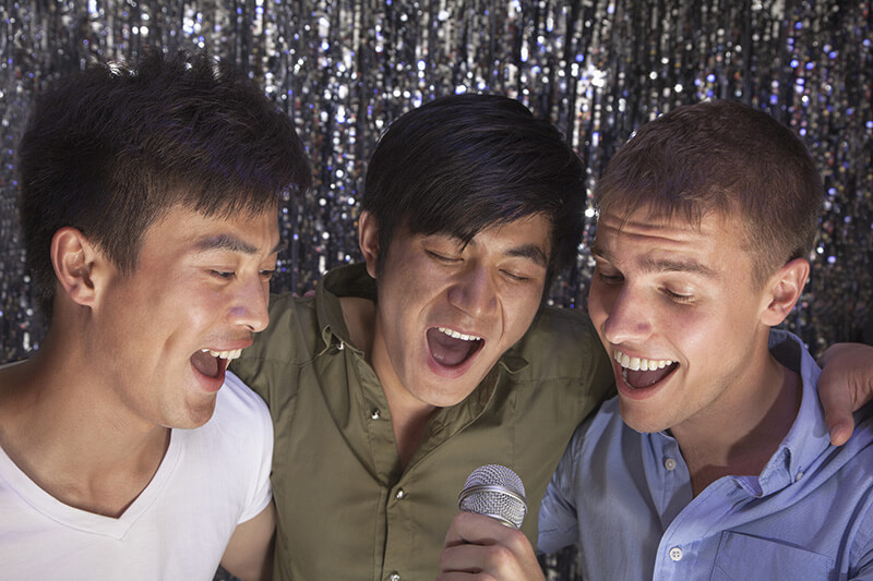 3 singers in front of silver sparkly background