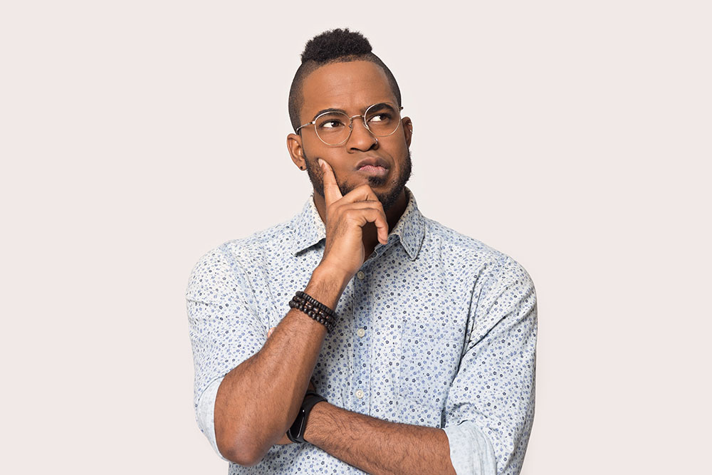 Thoughtful african guy thinking try solve problem pose isolated on grey studio background, worried black man in glasses feels concerned puzzled lost in thoughts pondering making decision concept image